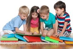 Barn med böcker på golvet Arkivfoto