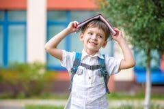 Barn med boken på hans head utomhus Arkivfoto