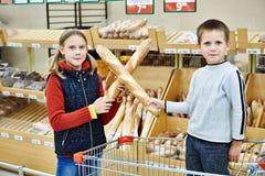 Barn med bröd i supermarket Arkivbild