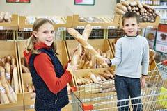 Barn med bröd i supermarket Arkivfoton