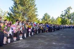 Barn med buketter av blommor skriva in sig i den första kvaliteten i skola med lärare och elever på en högtidlig linjal av skolan Arkivfoton