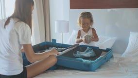 Barn med den lilla dottern som tillsammans samlar en resväska lager videofilmer