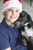 Barn med den Santa Claus hatten och den svarta hunden Royaltyfri Fotografi