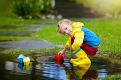 Barn med det pappers- fartyget i pöl Ungar vid regn fotografering för bildbyråer