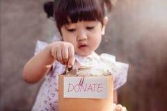 Barn med donationbegrepp 2 år gammalt barn som sätter pengar Coi Fotografering för Bildbyråer
