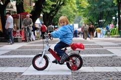 Barn med en cykel i en parkera Royaltyfria Bilder