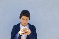 Barn med en mobiltelefon Arkivfoto