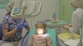 Barn med en moder på ett mottagande för tandläkare` s Flickan ligger i stolen, bak hennes moder Doktorn arbetar med lager videofilmer