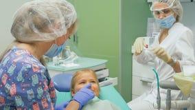 Barn med en moder på ett mottagande för tandläkare` s Flickan ligger i stolen, bak hennes moder Doktorn arbetar med fotografering för bildbyråer