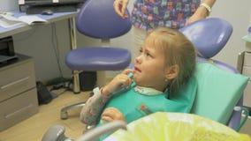 Barn med en moder på ett mottagande för tandläkare` s Flickan ligger i stolen, bak hennes moder Doktorn arbetar med stock video