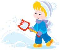 Barn med en snöskyffel Arkivbild