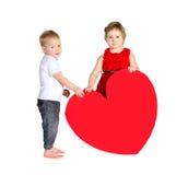 Barn med enorm hjärta som göras av rött papper arkivbild