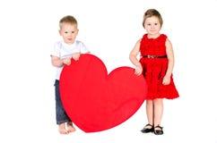 Barn med enorm hjärta som göras av rött papper Arkivfoton