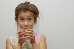 Barn med ett exponeringsglas av vatten Arkivbilder