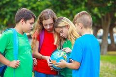 Barn med ett jordklot lär geografi Fotografering för Bildbyråer