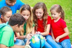 Barn med ett jordklot lär geografi Royaltyfri Foto