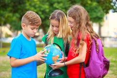 Barn med ett jordklot lär geografi Arkivbilder