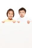 Barn med ett vitt bräde Arkivfoto