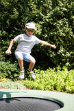 Barn med exponeringsglas som hoppar på en trampolin Royaltyfria Bilder