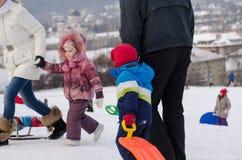 Barn med föräldrar som spelar i vinter, parkerar Royaltyfria Bilder