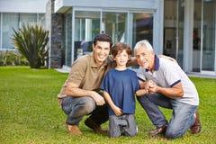 Barn med fadern och farfadern i trädgård Arkivbilder