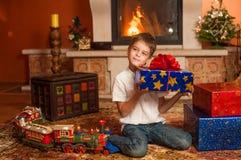 Barn med feriegåvor vid spisen Arkivfoto