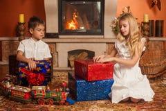 Barn med feriegåvor vid spisen Royaltyfri Fotografi