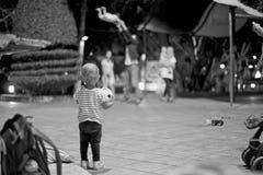 Barn med fotbollbollen som ser som en en annan familj som har gyckel på parkera arkivfoto