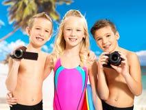 Barn med fotoet och videokameran på stranden. Royaltyfri Foto