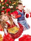 Barn med gåvaasken nära julgran. Arkivfoton