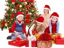 Barn med gåvaasken nära julgranen. Royaltyfri Foto