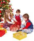 Barn med gåvaasken nära julgranen. Arkivfoton