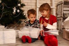 Barn med gåvor nära en julgran Fotografering för Bildbyråer