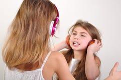 Barn med hörlurar som lyssnar till musik arkivbild