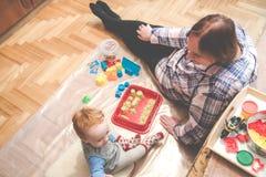 Barn med hans farmor som inomhus spelar royaltyfri fotografi