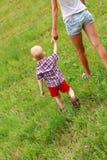 Barn med hans mom som går på den gröna ängen Arkivbilder