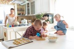 Barn med henne moder som förbereder kakor, stor familj casua Fotografering för Bildbyråer