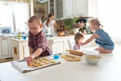 Barn med henne moder som förbereder kakor, stor familj casua Royaltyfri Fotografi