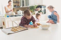 Barn med henne moder som förbereder kakor, stor familj casua Arkivbild