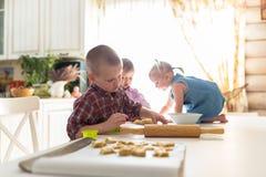 Barn med henne moder som förbereder kakor, stor familj casua Arkivfoto
