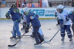 Barn med hockeypinnar som spelar hockey på festivalen arkivfoton