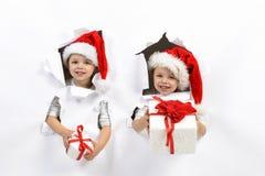 Barn med jultomten hatt och gåvor Arkivbild