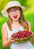 Barn med körsbär Liten flicka med nya körsbär Bärande tandhänglsen och exponeringsglas för ung gullig caucasian blond flicka royaltyfri fotografi