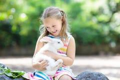 Barn med kanin kanin easter Ungar och husdjur arkivbilder
