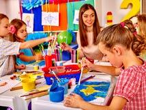 Barn med lärarekvinnamålning på papper i dagis Royaltyfri Bild