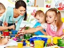 Barn med läraremålning. Arkivbild
