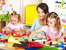 Barn med läraren på klassrumet. Arkivfoto