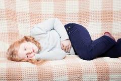 Barn med mageknip i soffa royaltyfria bilder