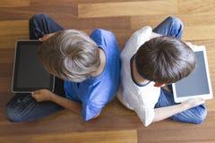 Barn med minnestavlaPC:N som hemma sitter på trägolv Top beskådar Utbildning som lär, teknologi, vänner, skola Arkivfoton