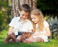 Barn med minnestavlaPC på sommar royaltyfri bild
